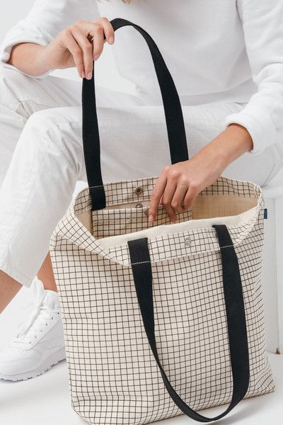 A perfectly simple canvas shopper tote from Baggu in a minimalist grid print. A roomy canvas bag with a top snap closure. Inner pocket with snap holds an iPhone, wallet or keys. Handles fit comfortably over shoulder. In premium recycled canvas cotton duck.