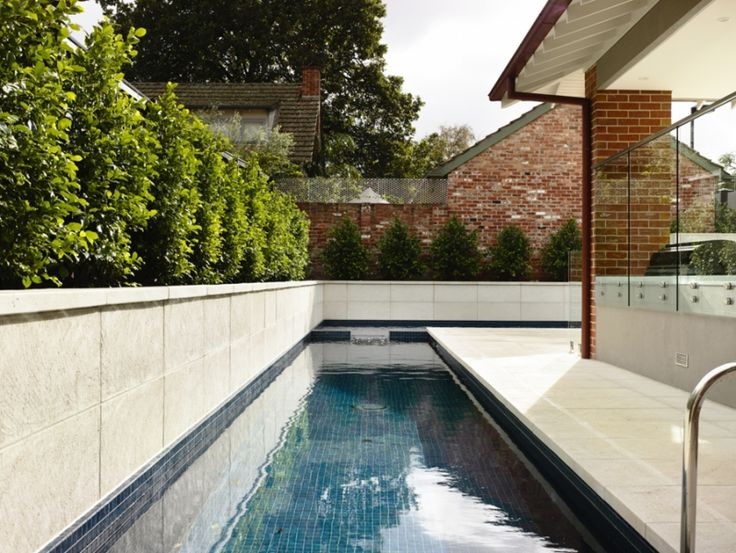 Long and narrow pool wrapping house in an L shape