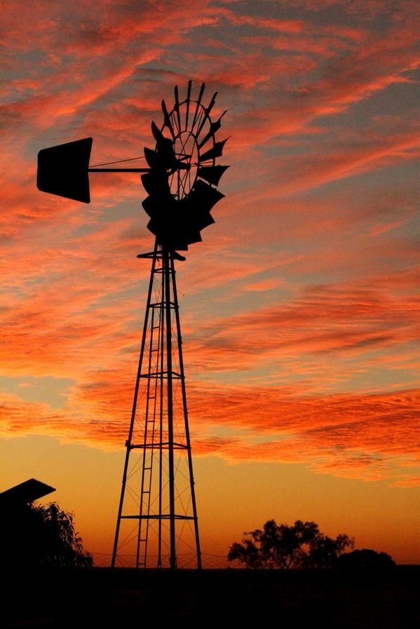 Australian windmill, sillhouetted against a beautiful red sunset.