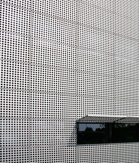 Office building with uniformly perforated facade panels Folding facade