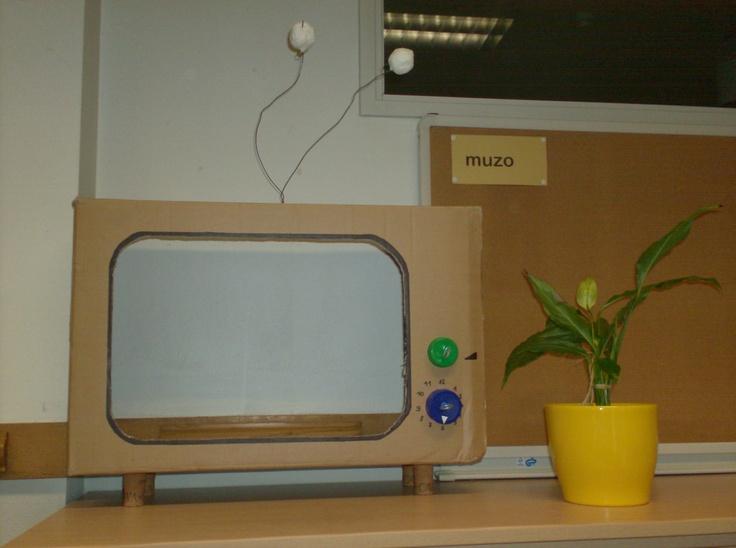 De kartonnen tv voor actua. Pootjes gemaakt van cavastopsels en de tv-knoppen zijn gemaakt van melkflesdoppen