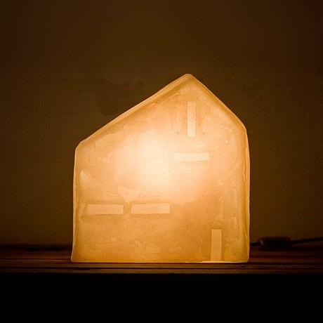 Una lampada a forma di cascina di un bianco candido che sembra di cera. Crea una luce calda, accogliente e intima. Racchiude un mondo di storie, quelle degli immaginari abitanti che occupano le sue quattro mura. Un complemento d'arredo essenziale, nato dalla riflessione sulle forme della città.Lampada da tavolo, Materiale: Resina, pigmenti e luce  Dimensioni: Lunghezza 17 cm Larghezza 12 cm Altezza 25 cm. La trovi su http://lovli.it/index.php/casine-cascina.html#