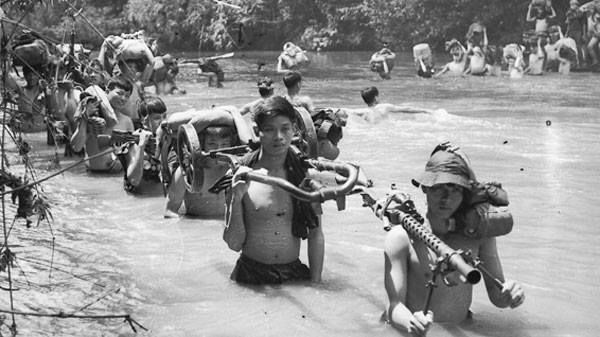 Viet Cong fighters crossing a river in the early 1960's. The man at the front of the column carries a surplus U.S. M1919A6 .30 caliber machine gun, most likely captured during the Korean war by the Chinese and then given to the North Vietnamese. he also appears to have some captured or surplus U.S. Army equipment over his shoulder.