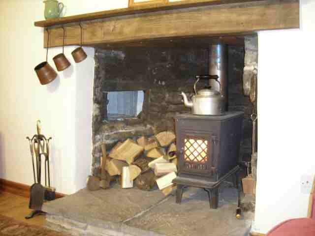 This is an old fireplace that has had a super cute wood stove put in. The hole in the left side of inglenook is an old bread oven.