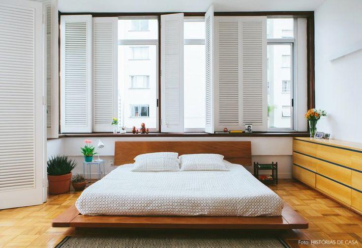 Quarto aconchegante com móveis de madeira, venezianas brancas e plantas.