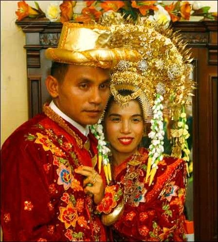 Roni Gustiawan dressed in traditional Indonesian red and gold finery and his bride Evi Susanti pose for a picture during their traditional wedding ceremony in Pariaman, Indonesia's West Sumatra province. The period immediately after the fasting month of Ramadan is considered an auspicious time for many Indonesian Muslims to marry.