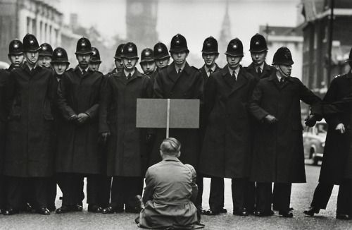 A lone anti-war protester confronts police in Whitehall during the Cuban Missile Crisis, London, England, United Kingdom, 1962, photograph by Don McCullin.