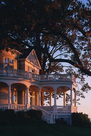 Summer evening at an old Victorian with porch and gazebo.