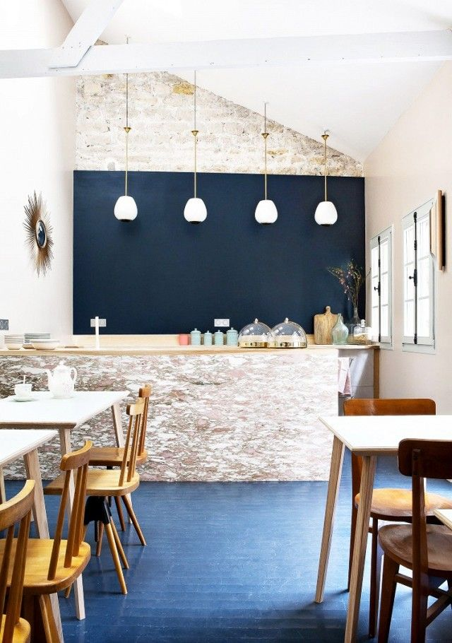 Hotel restaurant with a dark blue wall, exposed brick, retro pendant light and blue wood floors