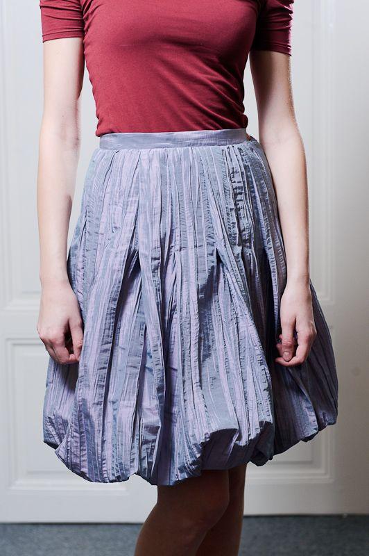Balonová sukně Sukně ze světle šedivého šanžánového mačkaného taftu. Hodně široká, s odšitými záhyby, do pevného pásku. Vypodšívkovaná, se skrytým zipem. Vzhledem k použitému materiálu je spíše společenská, než na denní nošení. Je možné na zakázku ušít i jinou délku nebo velikost.