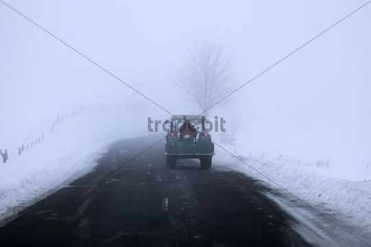 Tractor in a snow-covered winter landscape in the mist Belmicke Bergneustadt Oberbergischer Kreis North Rhine-Westphalia Germany Europe