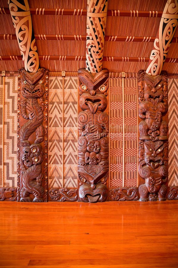 Carved Traditional Maori Figure, called Poupou, supporting the overhead rafters of the meeting house.  These are the 12th, 13th, and 14th on the left side after entering the house.  The twelth and thirteenth represent the style of the Ngati Porou tribe of the east coast north of Gisborne; the 14th represents the Rongowhakata tribe of Gisborne.   Te Whare Runanga, built 1940, Waitangi Treaty Grounds, Paihia, north island, New Zealand.  The woven panels on either side of the poupou are called…