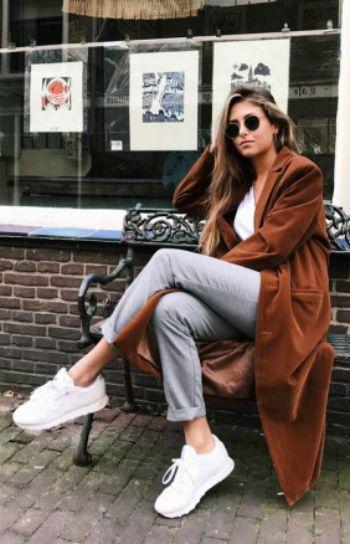 Noa Ismay de Vries + casual Spring outfit + full length velvet coat + white tee + grey slacks + white sneakers + sunglasses + edgy feel.   Trainers: Reebok.