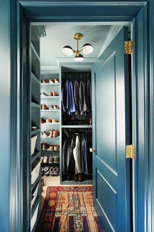 "Peak into a blue closet displaying ""His"" custom stacked rails, shelves and built in blue shoe racks lit by a black and gold chandelier."