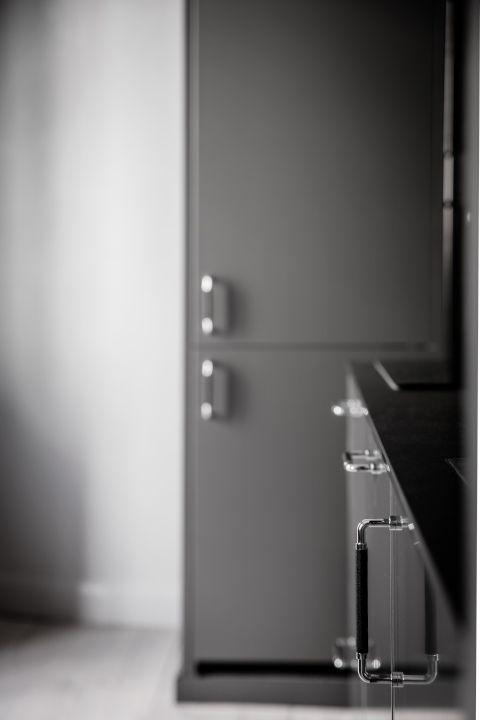 En mörkare grå färg på snickerierna bryter fint av mot den svarta bänkskivan och handtag i svart läder | Ballingslöv