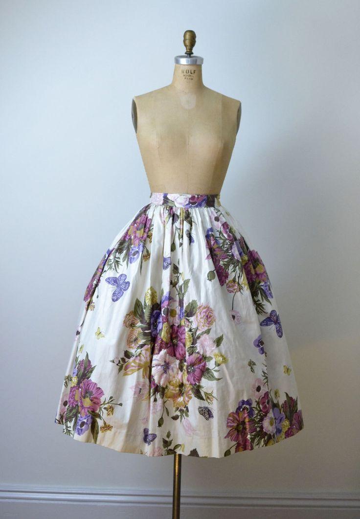 Een jurk van de jaren 1950 ingesteld met vrij gewatteerde en prong ingesteld Strass-accenten. De ingerichte katoenen blouse heeft een v-hals, vouw over kraag, dubbele buste darts, prinses naden en paarse grosgrain lint dat aan de achterkant bindt. Het vastmaakt met een ritssluiting zijkant staal. De omvangrijke rok is gevormd van een prachtige crème gepolijst katoen met een vet bloemenprint. Het vastmaakt aan de achterkant met een metalen rits en haak & eye sluitingen.  -Grootte groot- B...