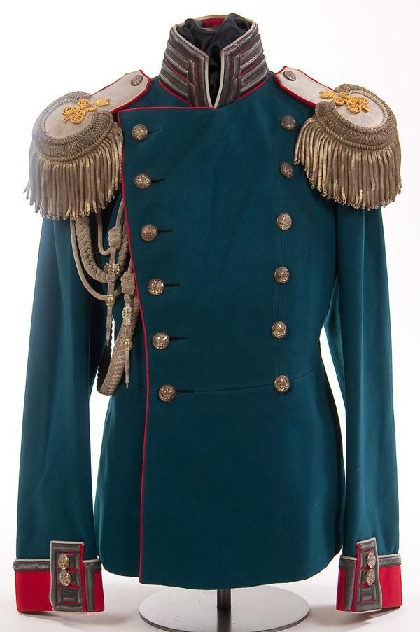 Blue wool double breasted tunic with red collar, cuffs and piping of an Imperial Russian tunic of a War Ministry Officer acting as Aide de Camp on the Tsar's Staff, circa 1907.  Collar and cuffs piped white with silver Litzen. Has a matched pair of silver epaulettes, faced in red, with applied gold Nicholas II crowned ciphers and with silver cord adjutant's aiguillette with silver crowns and points.