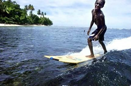 Paga Hill Estate, Paga Hill Development Company A boy surfs off Lido Village, Vanimo, in north-west Papua New Guinea on a board donated from Sydney.
