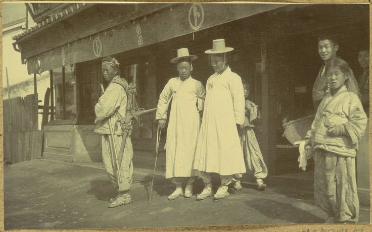 [Korean laborer and middle class in front of store] 1904. Two middle class men in 'hanbok' ( traditional Korean clothes). A laborer with an A-frame on his back is standing by. 'The human porter who was the most ubiquitous carrier of heavy loads, the A-frame on his back piled high with goods. Willard D. Straight/Early U.S.-Korea Diplomatic Relations, Cornell Univ Library
