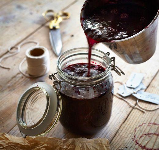 Marmelade wird aus einem Edelstahltopf in eine KORKEN Dose mit Deckel aus Klarglas gegossen.