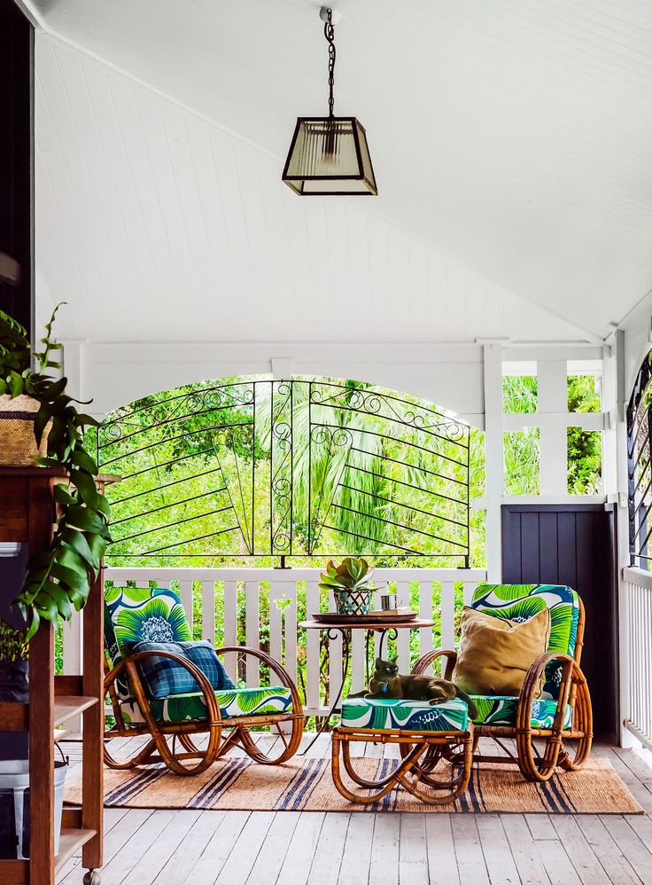 Queenslander - outdoor entertaining area: pale limewashed timber decking, white railing/balustrade, black metal decorative security screen, leafy outlook, cane/wicker rocking chairs and ottoman, high sloping ceiling with white wooden panelling, trapezoidal prism pendant light