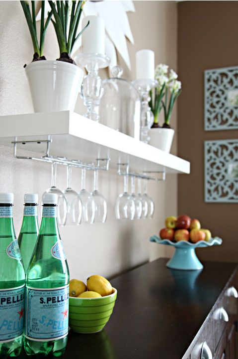 Ikea floating shelves with places to hold wine glasses. Great idea for our bar!