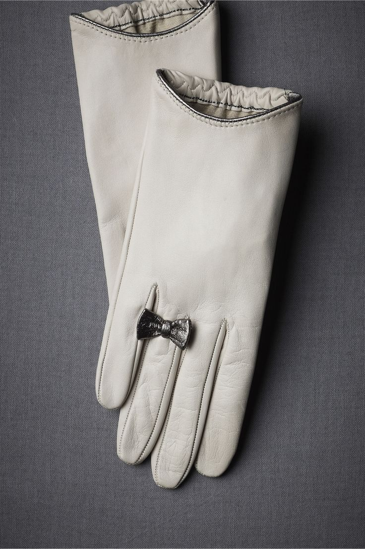 Platinum Promise Gloves. This wrist-barring pair keeps hands handsomely under wraps; a single shining bow adds flair. From Buscarlet. Leather; silk lining. Italy.