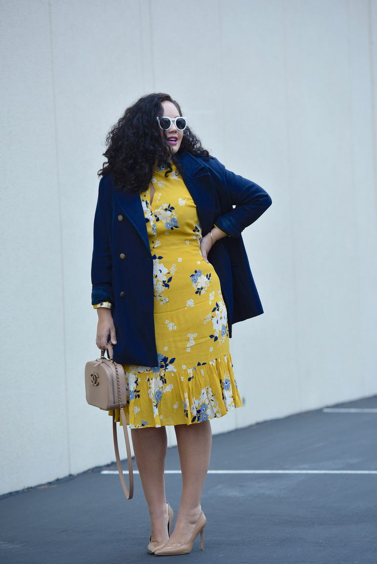 Girl With Curves blogger Tanesha Awasthi wearing an Old Navy yellow floral Dress and navy peacoat.