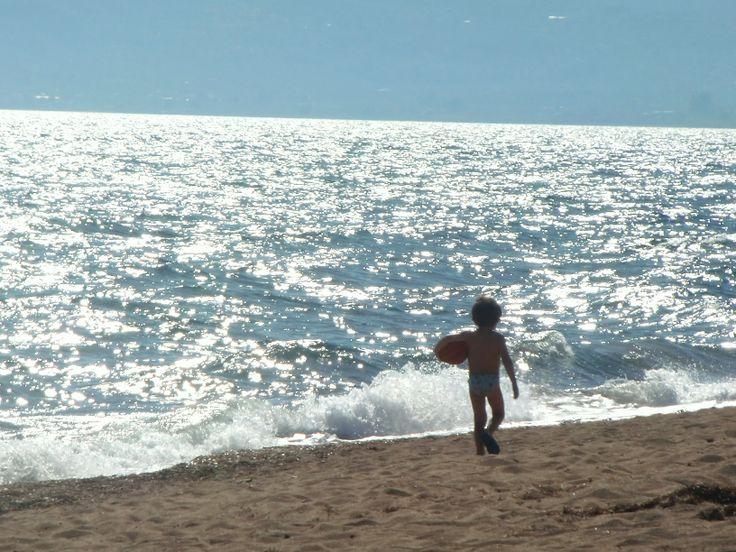Boy walking beach in Kalamata Greece