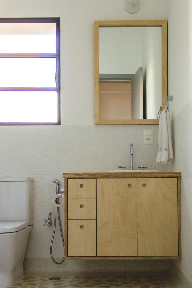 banheiro com piso em granilite gabinete em compensado naval com puxador furo espelho com moldura em madeira arandela de lâmpada aparente reka vaso sanitário roca