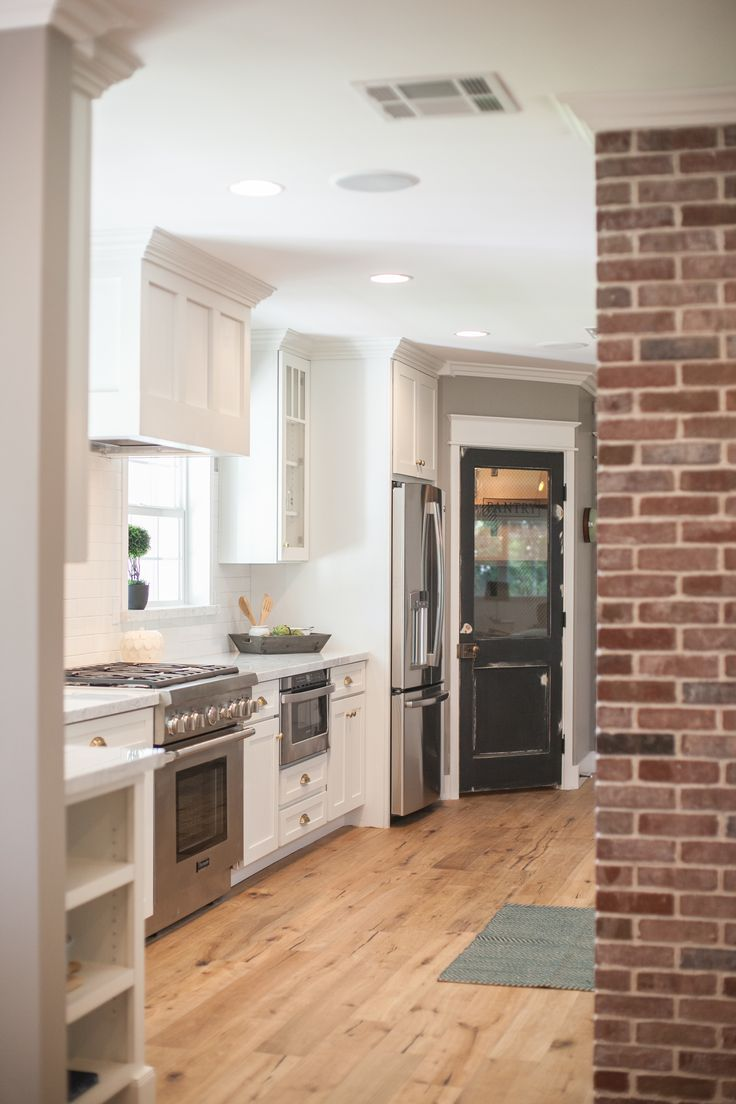 White shaker cabinetry, carrara marble countertops, signature vintage pantry door - by Rafterhouse.