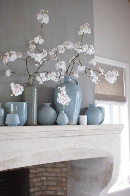 Blauwe vaasjes tegen een grijsblauwe muur voor een rustige en ruimtelijke styling