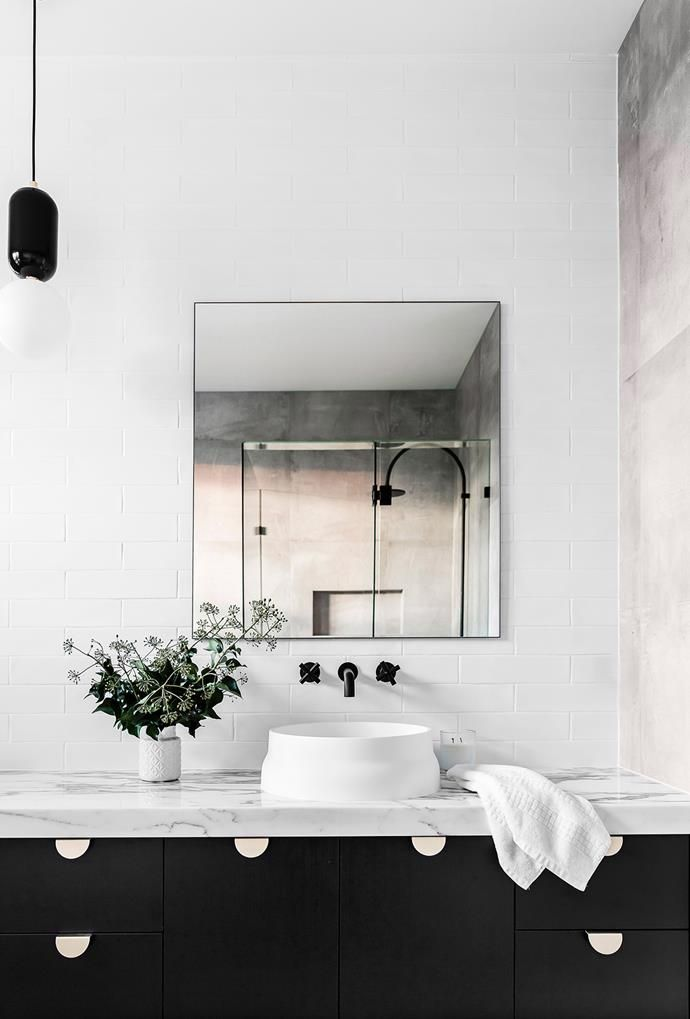 A rendered concrete wall adds a welcome contrast to this otherwise black and white space. Ticking boxes in both style and durability, this parred-back bathroom would work well all kinds of styling options. *Photography: Maree Homer / Bauer Syndication*
