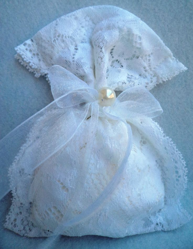 Pouch made of soft white lace and decorated with an organtza ribbon and a white pearl.