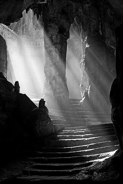 Light; In this photo bright light gleams through the opening in a cave like structure and down a stone staircase. The light fills large portions of the picture although leaving some shadowy areas as well.