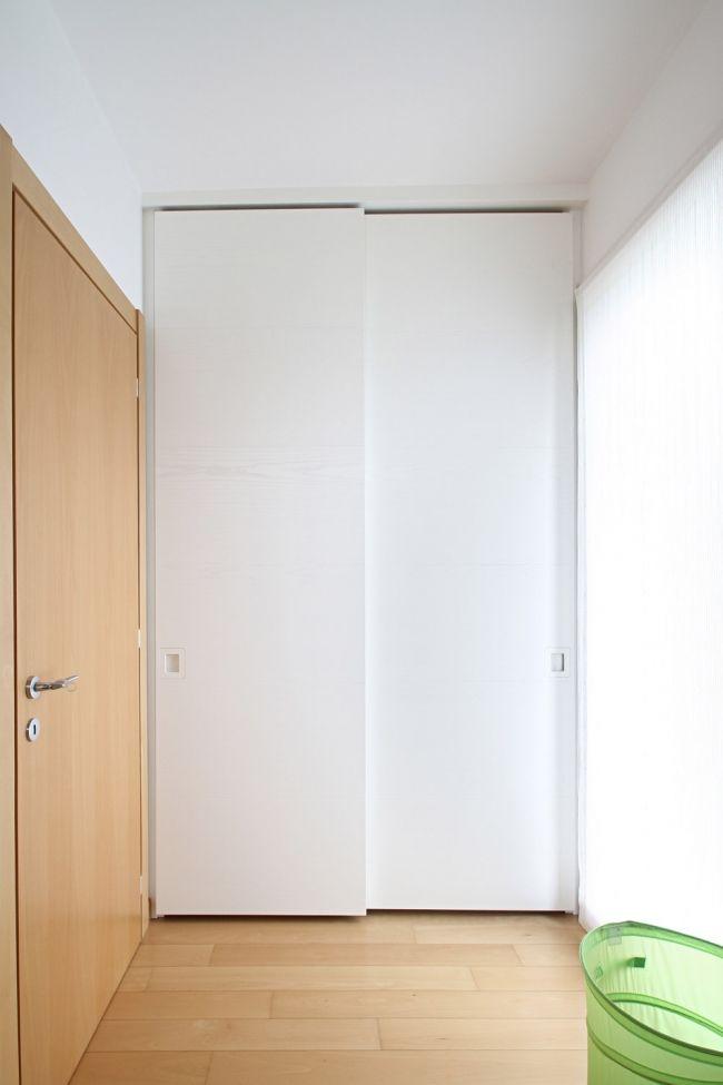 Ambientazione dell' armadio a muro su misura a 2 ante scorrevoli in frassino spazzolato con venatura continua, laccato bianco. Completo di maniglia inserita nello spessore del legno.