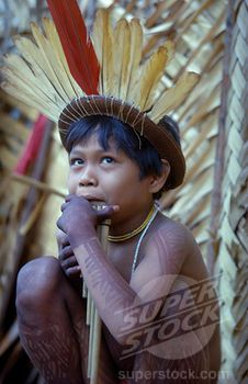 Colombia, Vaupes Region, Tukano Tribe, Young Boy Playing Panpipes Outside Maloca Prior To A Festival. Painted With Deep Purple We Leaf Dye And Wearing Crown Of Red Macaw And Yellow Toucan Feathers