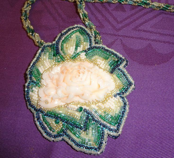 Questo è un ciondolo che ho realizzato per i miei 50 anni! Ho ricamato con perline giapponesi delle foglie intorno ad un cabochon di corallo rosa intagliato a mano, di provenienza cinese. Ho poi realizzato la catenella su modello di Sonoko Nozue