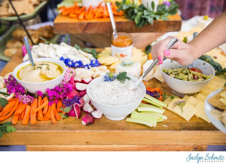 Jaclyn Schmitz Photography - Far: The Farmhouse provides amazing cocktail hour and meal entrees for your wedding. This photo is one of the most colorful and amazing cheeseboard spreads I've ever seen at a wedding. Multiple levels of carefully and beautifully arranged cheese, spreads, jellies, veggies, and fruits adorn wooden boards atop wine crates. Location: 139 Bank St, Burlington, VT 05401.