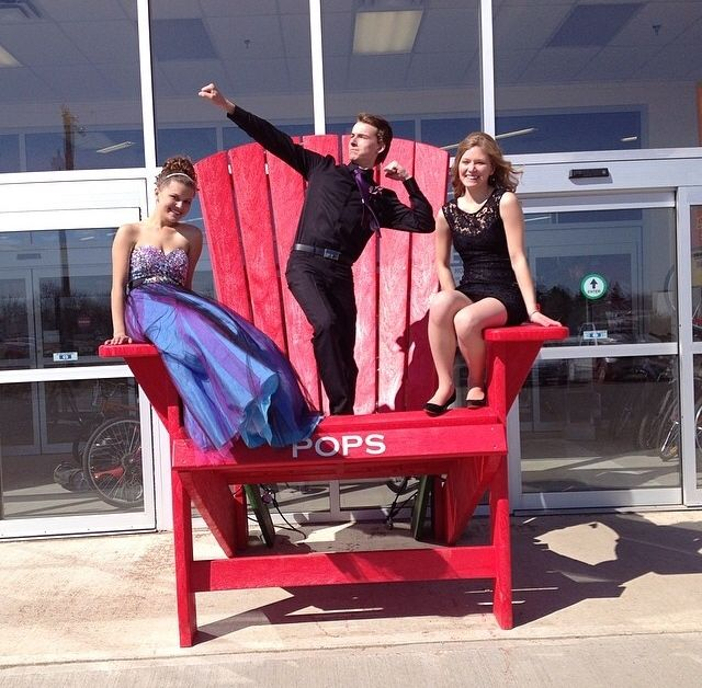 """Leann Peyre, Bryce Shunter and Nicole Peyre, share holders kids posing on the """" BIG RED CHAIR"""" on Leann's graduation day."""