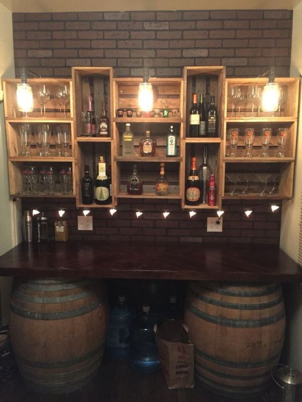My bar build. Got the wine barrels from a flea market and built the countertop and crate shelves out of pallet wood. The lights are black gas pipe with mason jars and Edison light bulbs by keisha