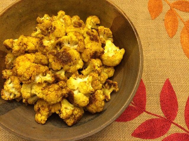 1 head of cauliflower, cut into uniform florets ¼ cup coconut oil, melted 2 tsp. curry powder 2 tsp. garlic powder 1 tsp. turmeric Juice of ½ lemon Pinch of Himalayan sea salt