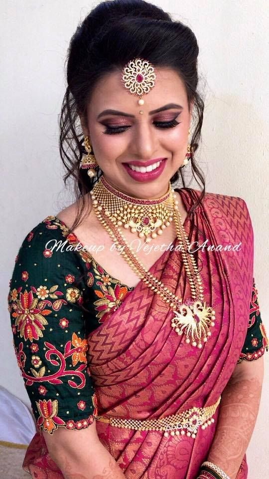 Pretty in pink! Nandita is all smiles after her bridal makeover for her reception. Hair and makeup by Vejetha for Swank. South Indian bride. Indian bridal makeup. Berry lips. Eyemakeup on fleek. Bridal hairstyle. Saree blouse design. Bridal silk saree. Bridal jewellery. Maang tikka.