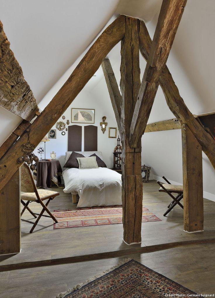 Une chambre d'amis sous combles. Malgré la forte pente du toit et la contrainte d'une charpente bois très présente, les propriétaires ont su installer une chambre pleine de charme dans un style campagne bohême.
