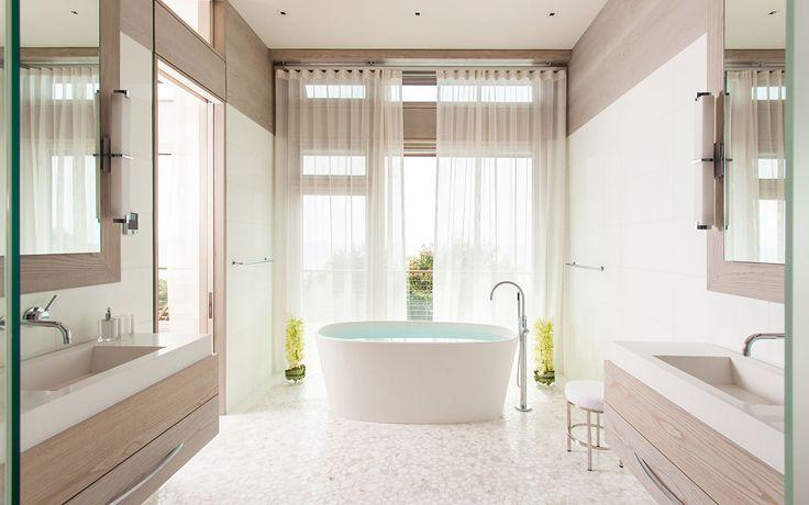 Modern style custom built Cape Cod bathroom with freestanding bath, tile flooring and abundant natural lighting. By Cape Associates, Inc.