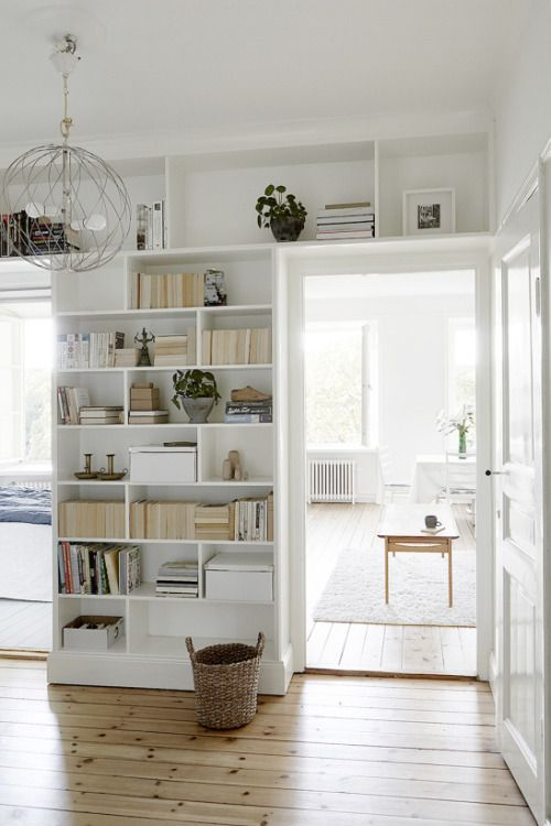 Heller Raum mit glänzendem Holzboden und weißem Bücherregal