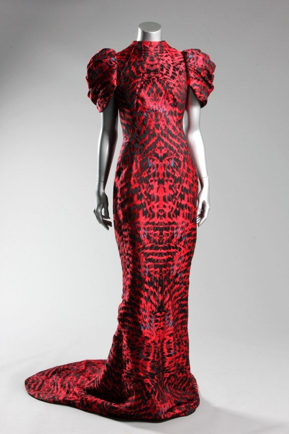 Alexander McQueen feather-weave gown, probably pre-collection, Autumn-Winter 2009, labelled and size 44, the princess-line gown with seams radiating from the high neck which traverse the hips and meet at the centre back, culminating in a large swagged bustle, the skirt narrowing again before finishing with a fish-tail hem