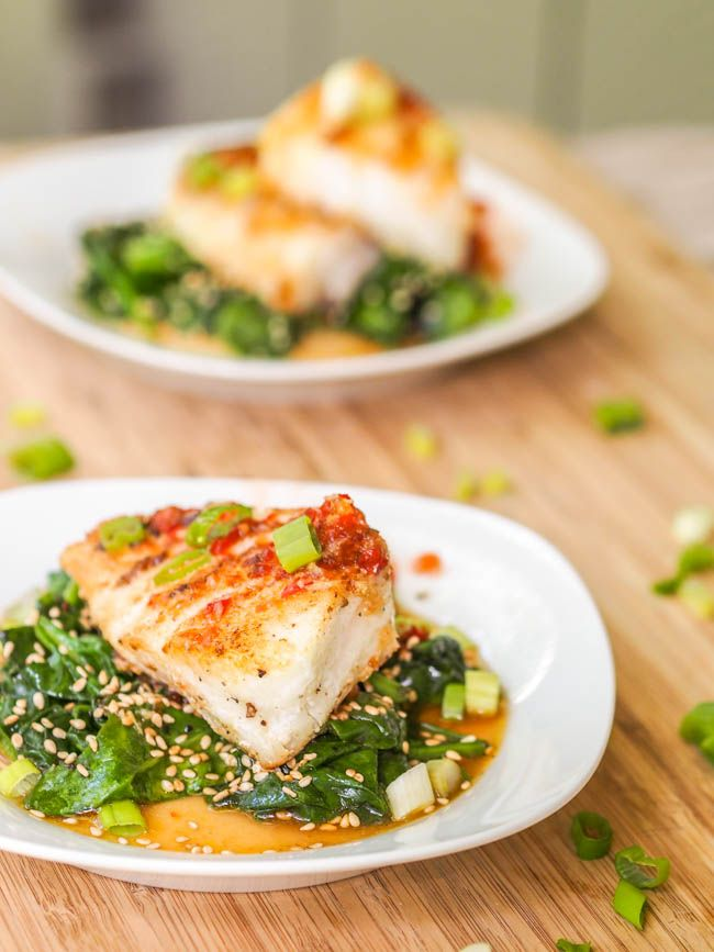 Seared Chilean Sea Bass filet served atop wilted sesame spinach and drizzled with a spicy, sour sweet Vietnamese inspired sauce. Gluten-Free and Dairy-Free.