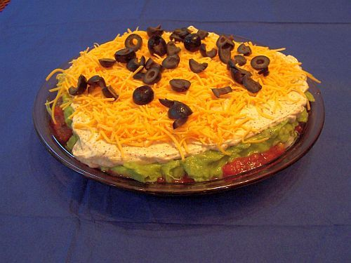 This Mexican dip recipe is always a crowd-pleaser. Made with lettuce, refried beans, cheese, guacamole, salsa and sour cream, this Mexican 7 layer dip recipe has all the flavors of good Mexican food. Black olives top off this tasty Mexican dip recipe.