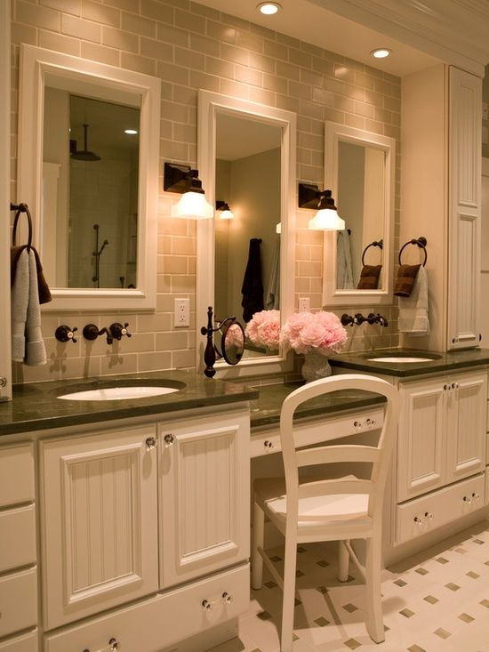 This sit-down makeup counter — nestled between two single vanities — features its own hanging mirror, pullout drawer for additional makeup and accessory storage and two sconces for proper lighting. To create a true contemporary look, designer Shane Inman added a gray, subway-tiled backsplash on the back wall and oil-rubbed bronze fixtures to contrast with the surrounding white cabinetry..